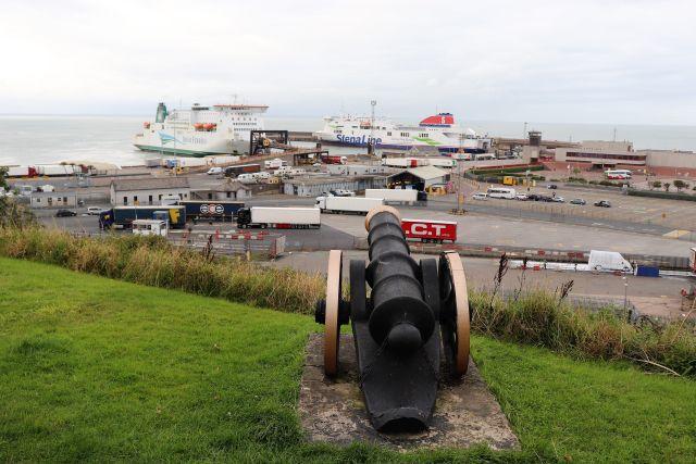 Auf grünem Rasen steht erhöht über dem Hafen von Rosslare eine alte Kanone und blickt in Richtung zweier Fährschiffe.