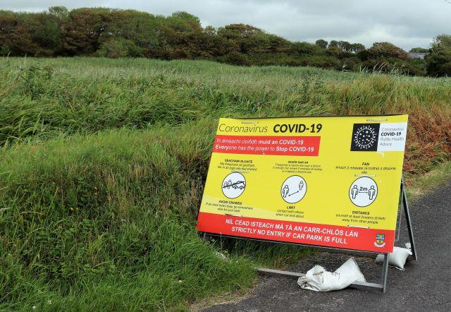 Gelb-rotes großes Warnschild zu Corona. Die üblichen Hinweise wie Abstand halten. In englischer und irischer Sprache. Umgeben von grünem Schilf.