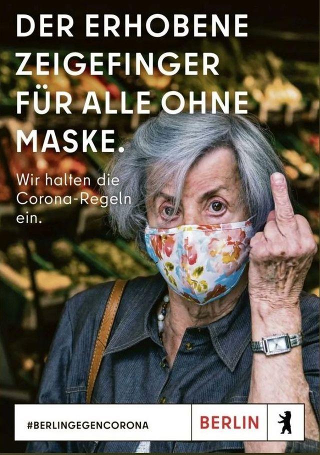 Eine ältere Frau mit bunter Mund-Nasen-Maske und grauen Haaren zeigt den Stinkefinger (Mittelfinger).