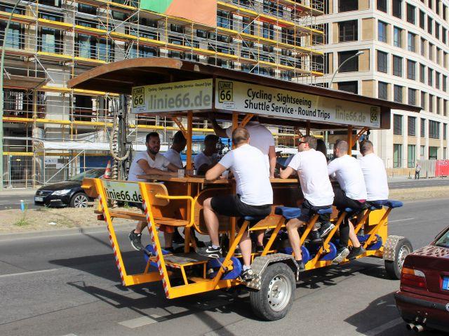 Sechs Männer sitzen auf einem rollenden Biertisch mit Bänken und fahren durch Berlin.
