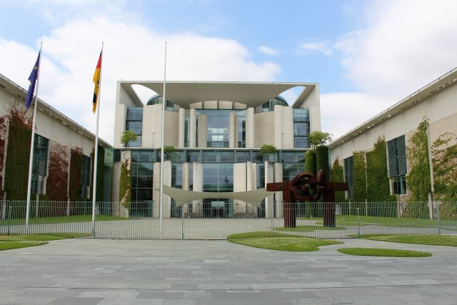 Das Bundeskanzleramt in Berlin: Es dominiert Beton mit Glas. Im Vordergrund ein Metallgitter. Links die Fahnen der EU und von Deutschland.