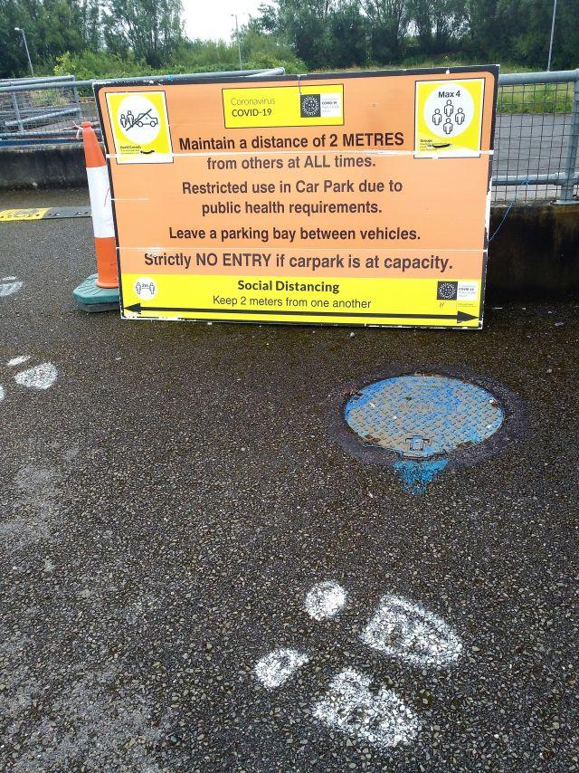Parkplatz in Irland mit weißen Fußabdrücken für die Richtung. Ein gelb-orangenes Plakat macht Vorgaben zum Abstand. Auch bei Fahrzeugen soll jeder zweite Platz freibleiben.