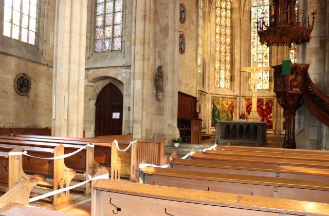 Abgesperrte Kirchenbänke aus Holz. Rechts ein großes Kreuz, daneben die Kanzel.