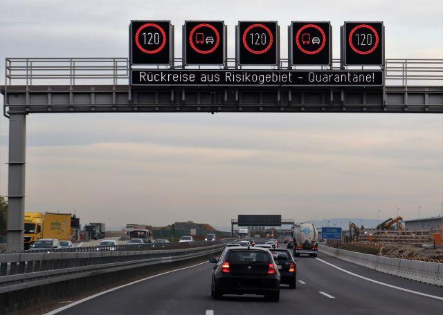 """Schilderbrücke über einer Autobahn am Abend. Angezeigt wird die Geschwindigkeit 120 km/h und darunter in hellen Leuchtbuchstabven: """"Rückreise aus Risikogebiet – Quarantäne!"""""""