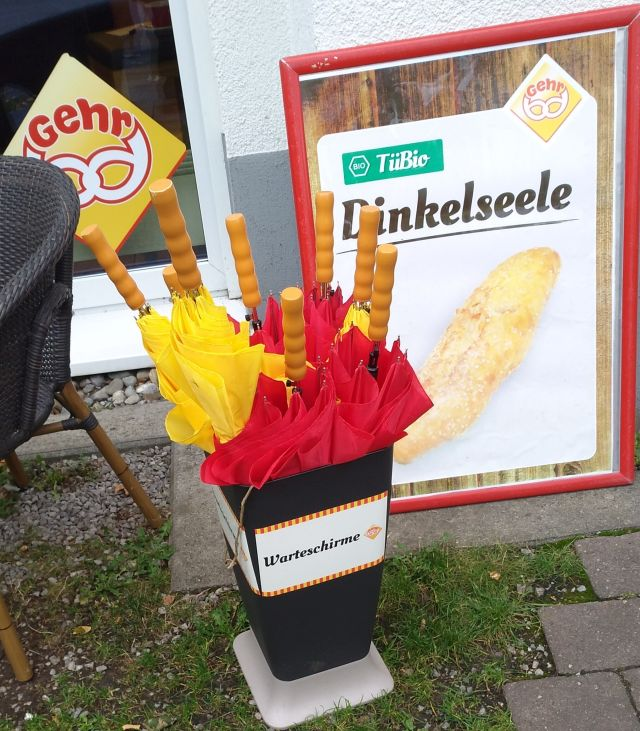 Eine Bäckerei stellt in Tübingen Schirme für Käufer bereit, die wegen Corona vor dem Laden anstehen müssen.