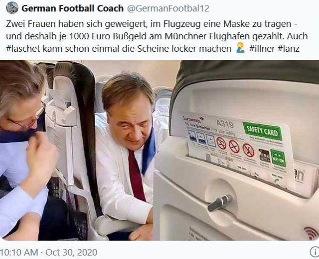 Armin Lascht beugt sich nach hinten und spricht mit einer anderen Person, die hinter ihm im Flugzeug sitzt. Laschet trägt keinen Mund-Nasen-Schutz.