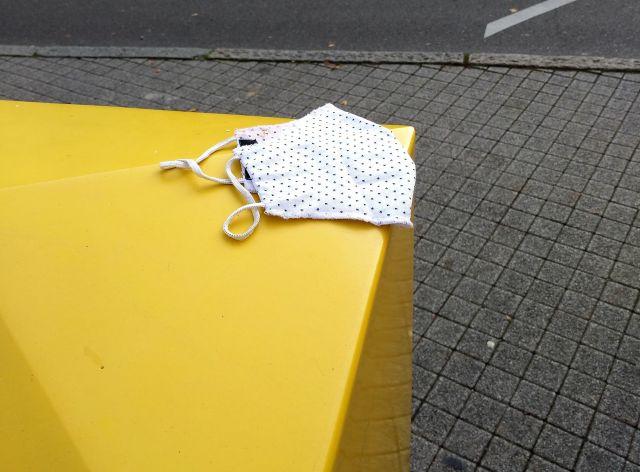 Weiße Corona-Maske auf einem gelben Briefkasten.