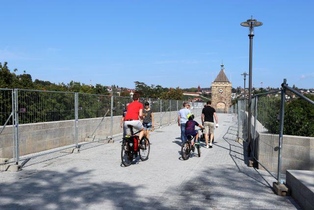 Radfahrer und Fußgänger auf einer Brücke. Im Hintergrund ein mittelalterlicher Turm.