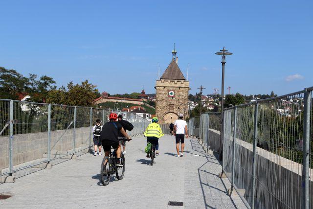 Heller Belag auf einer Brücke. Fußgänger und Radfahrer. Links und rechts hohe Bauzäune Im Hintergrund ein Turm aus Stein.