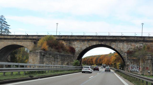 Eine Brücke aus Steinquadern über einer insgesamt vierspurigen Bundesstraße. Auf der Brücke sind Bauzäune zu sehen.