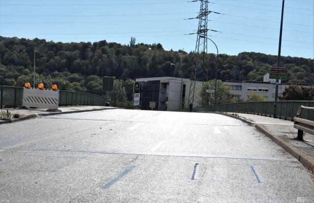 Eine mehrspurige Brücke im Sonnenlicht. Keine Fahrzeuge. Im Hintergrund ein weißes Parkhaus.