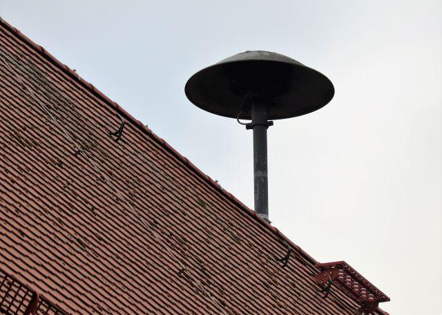 Eine Sirene auf einem roten Ziegelach. Diese Sirene ist noch von der herkömmlichen Bauart: Wie ein umgestülpter tiefer Teller auf einem Metallmast.