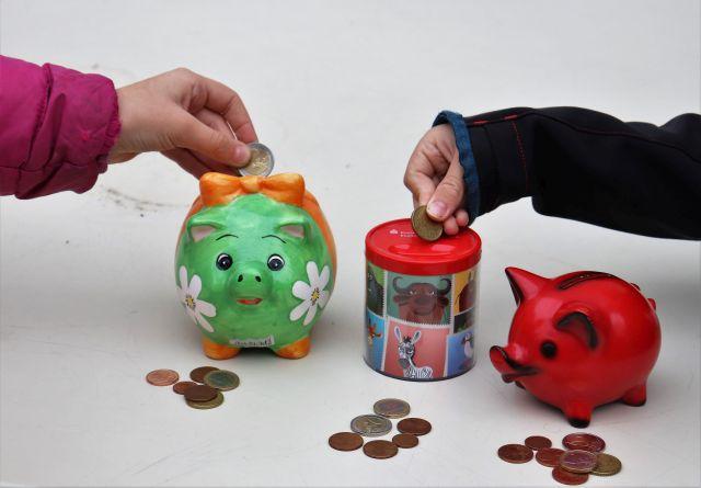 Ein grünes und ein rotes Sparschwein sowie eine Spardose. Zwei Kinderhände werfen Münzen ein.