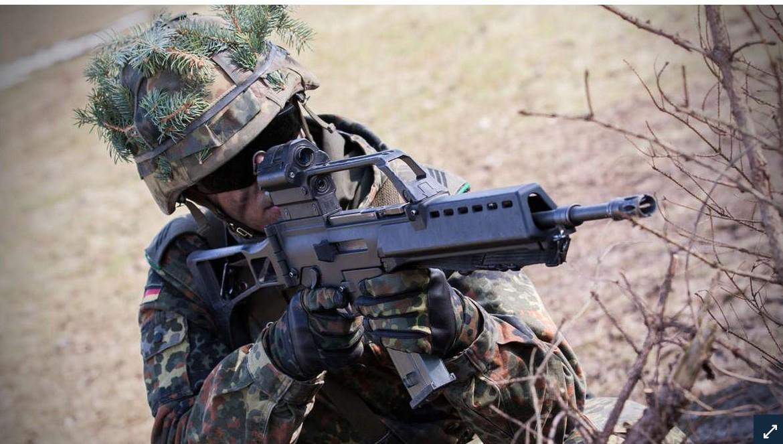 Getarnter Soldat mit Helm und dem Sturmgewehr G36.