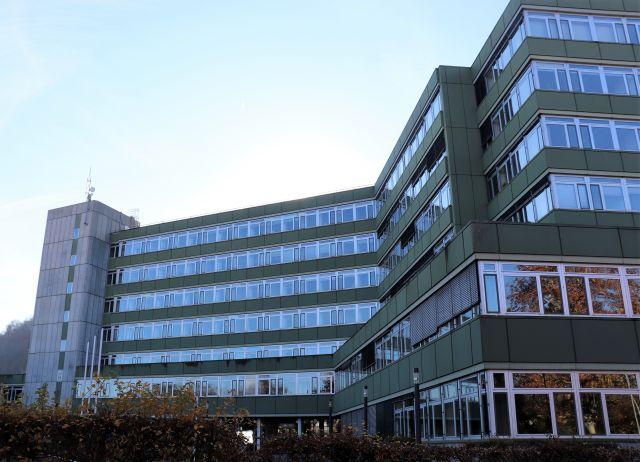 Ein mehrstockiges Gebäude mit vielen Fenstern und grünen Fassadenteilen. Links turmartig ein Gebäudeteil in grauem Beton.