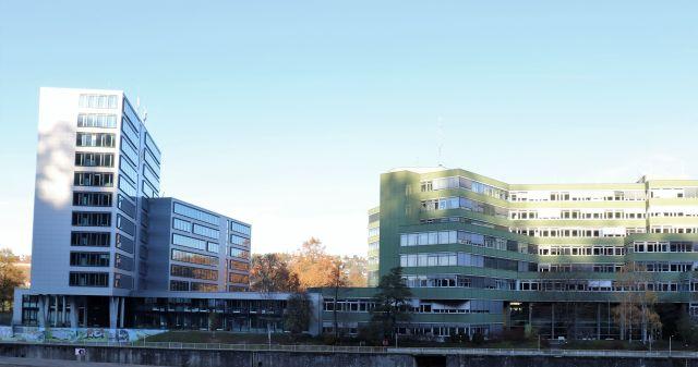 Alter und neuer Teil des Landratsamts Esslingen. Jeweils Beton und große Fenster. Der Altbau mit grünen Fassadenteilen, der Neubau in grau.
