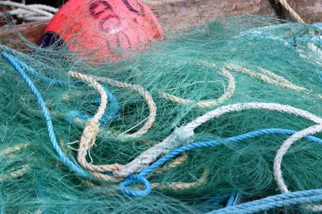 Engmaschiges grünes Netz am Kai liegend mit einer großen roten Boje.