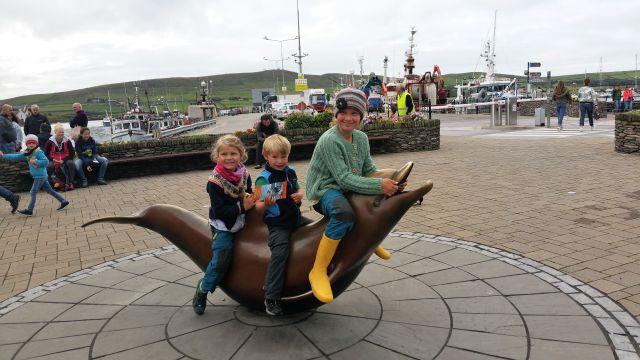 Drei Kuinder sitzen auf der Statue von Fungie. Im Hintergrund der Hafen.