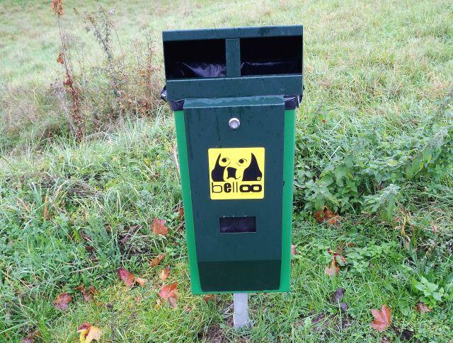 """Grüner Behälter für Hundekotbeutel mit einem schwarzen Hundegesicht auf gelbem Untergrund. Aufschrift """"belloo""""."""