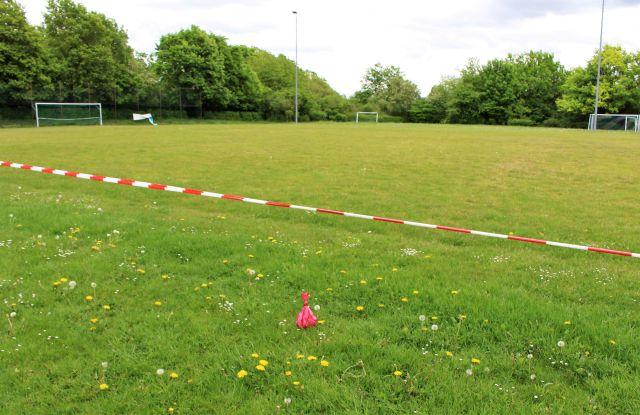 Wegen Corona mit einem rot-weißen Band abgesperrter Sportplatz. Vorne im Bild ein roter Hundekotbeutel.