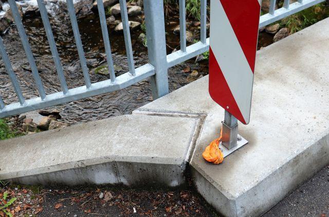 Hundekotbeutel in orangener Farbe. Abgelegt an einer rot-weißen Warnbake auf einer kleinen Betonbrücke. Darunter ist ein breiter Bach zu sehen.