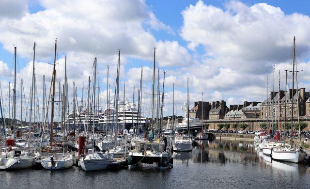 Jachthafen mit großen Segelbooten, dahinter zwei Kreuzfahrtschiffe und links die Stadtmauer von Saint-Malo.
