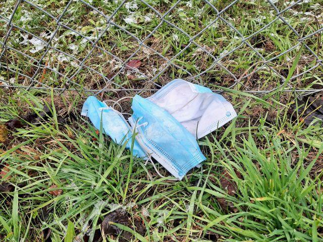 Drei weiß-blaue Corona-Masken im Gras neben einem Feldweg.