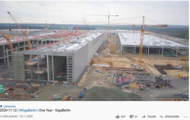 Foto von einer Drohne aufgenommen, das eine gewaltige Fabrikhalle in der Bauphase zeigt. Im Hintergrund noch Wald.