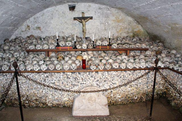 Ein Beinhaus: In der Mitte der Wand ein Kreuz, darunter Schädel und in der unteren Schicht Knochen sorgsam gestapelt.