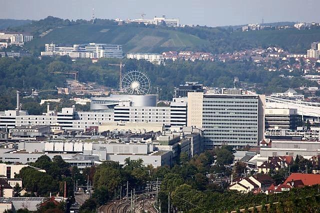 Blick aus Richtung Esslingen gen Stuttgart auf das Mercedes-Benz-Werk Untertürkheim. Dort ist ein Hochhaus und dahinter ein Riesenrad zu sehen.