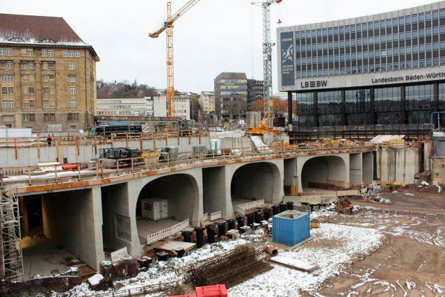 Verschiedene Tunnelenden aus Beton, die zum zukünftigen unterirdischen Hauptbahnhof in Stuttgart führen. Darüber links und rechts Gebäude.