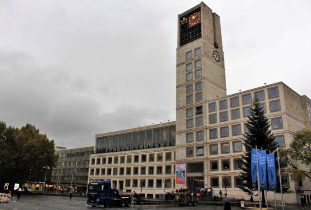 Blick auf das nach dem Zweiten Weltkrieg erbaute Rathaus in Stuttgart. Es ist mit hellem Stein verkleidet und hat einen hohen Turm. Davor ein Lkw, der gerade einen Weihnachtsbaum angeliefert hat. Dieser steht bereits