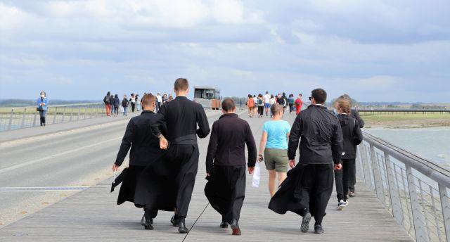 Vier Mönche in schwarzen Kutten und zahlreiche buntgekleidete Touristen gehen in Richtung Festland.