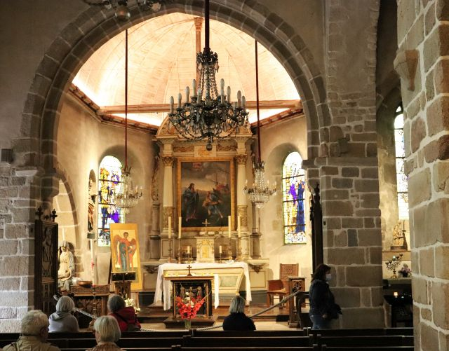 Blick ins Innere der Pfarrkirche Saint-Pierre auf dem Mont-Saint-Michel. Der Altar ist hell erleuchtet, in den Bänken sitzen einige Personen.