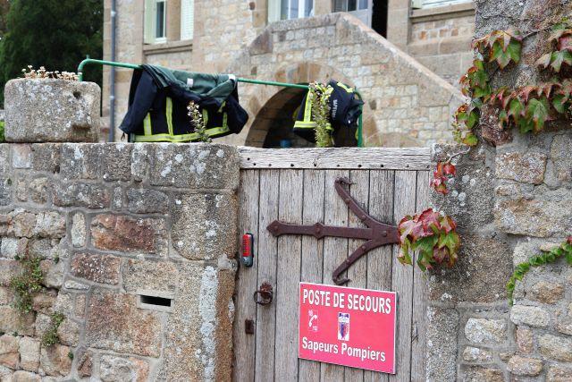 """Holztür mit rotem Schild: """"Poste de Secours. Sapeurs Pompiers"""". Kleine Feuerwehrstation. Zwei Einsatzjacken hängen auf einer Wäschestange."""