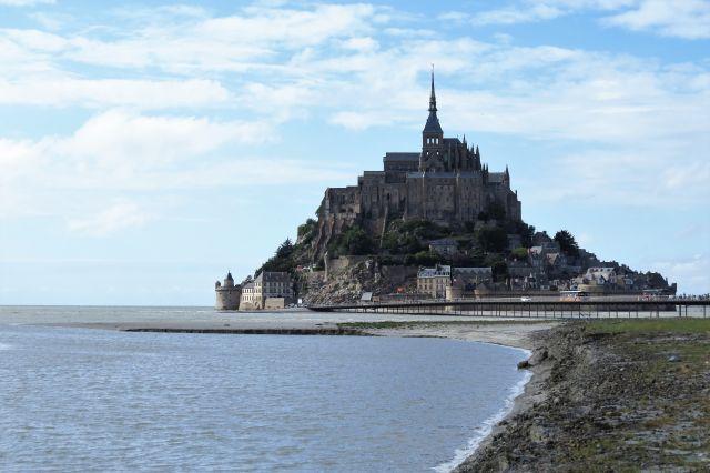 Mont-Saint-Michel: Der Berg mit einer Kirchenspitze ganz oben und zahlreiche Gebäude aus behauenen Granitsteinen. Links eingetragener Sand, rechts das Meer.