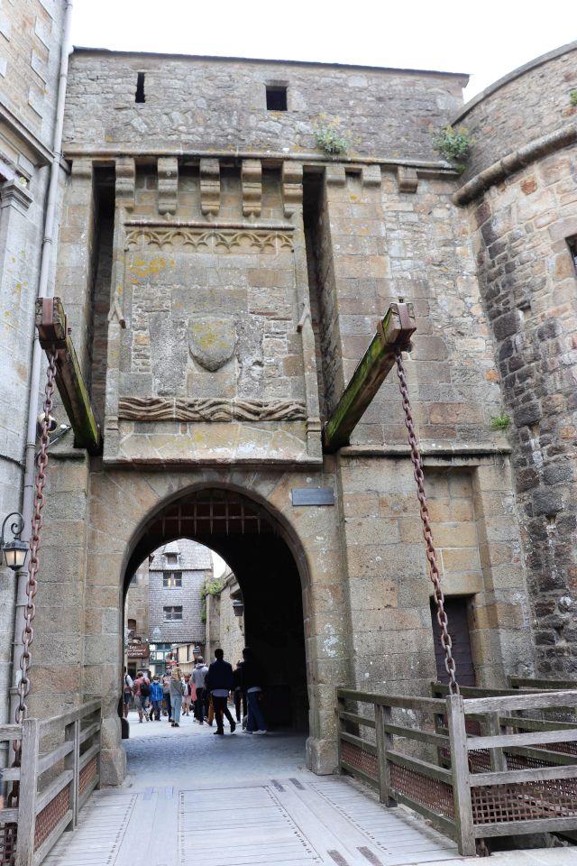 Ein Tor in einer Mauer aus Steinquadern mit einer vorgelagerten Zugbrücke. Die schweren Eisenketten sind deutlich erkennbar.
