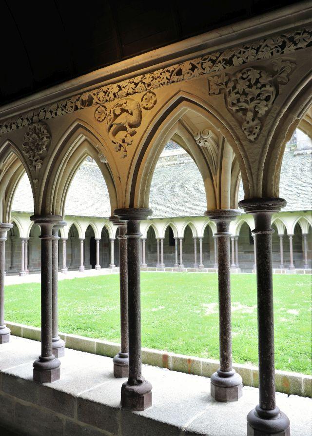 Der Kreuzgang. Steinerne Säulen mit verzierten Kapitellen. In der Mitte nur grünes Gras und keine weiteren Pflanzen.