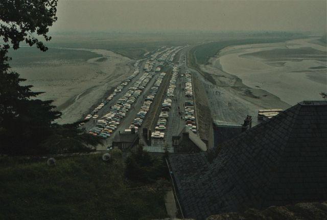 Die frühere Situation am Mont-Saint-Michel: Zahllose Pkw parken in mehreren Reihen direkt am Mont-Saint-Michel. Der Blick wird vom Klosterfelsen in Richtung Damm und Festland gezeigt.