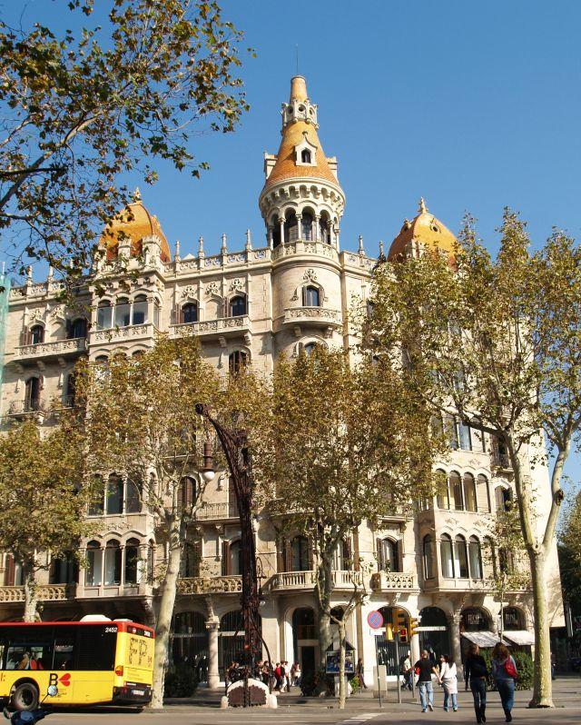 Bäume in Barcelona vor einem historischen Gebäude.