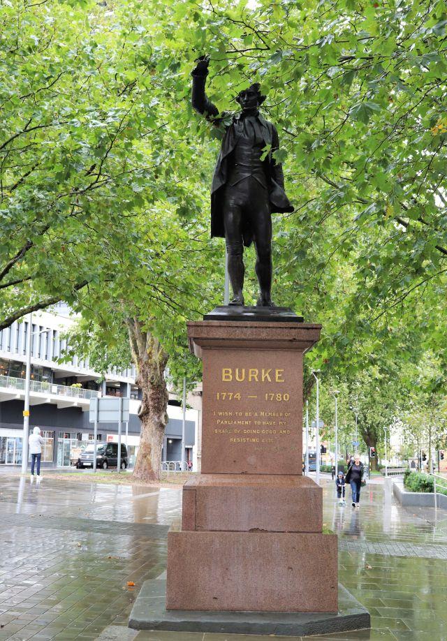Eine Statue, die Edmund Burke zeigt, auf einem braunen Steinsockel. Über dem Denkmal ein grünes Dach aus Blättern.
