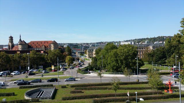 Bäume an einem vielbefahrenen Platz in Stuttgart. Zu sehen ist auch das Alte Schloss.