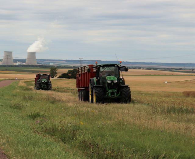 Zwei schwere Traktoren mit Anhängern. Im Hintergrund die Kühltürme eines Kraftwerks.