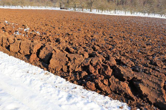 Ein tiefgepfügtes Feld. Die braune Erde ist tief aufgerissen und umgeworfen. Ringsum liegt Schnee.