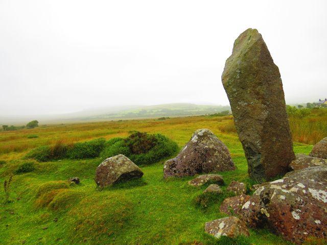 Ein aufrecht stehender Stein, umgeben von kleineren Felsen auf einer Grasfläche.