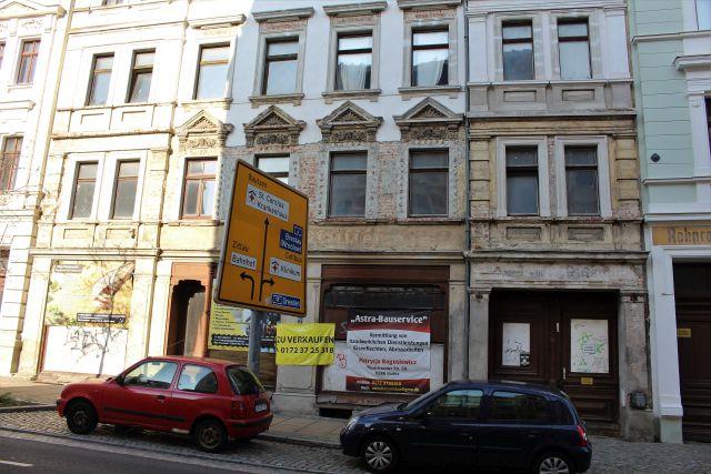 Ältere und heruntergekommene Fassade mit einem Transparent 'Zu verkaufen'.