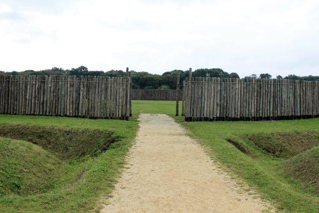 Ein geschotterter Weg führt direkt auf ein Tor in einer Holzpalisade zu. Im Hintergrund sieht man, dass auch dort Holzstämme in den Boden gerammt wurden.