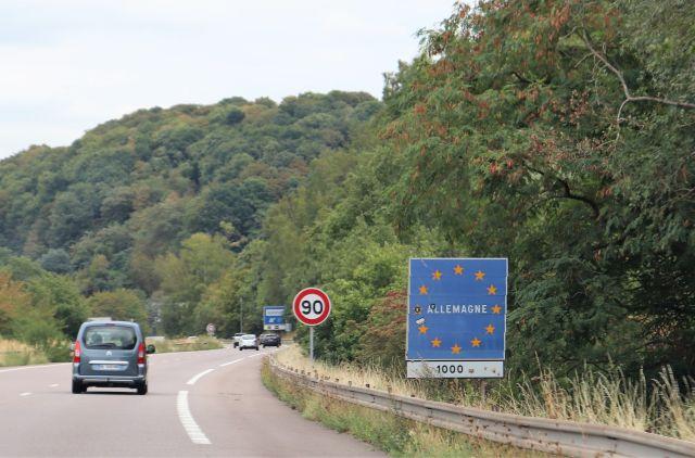 """Französisch-deutsche Grenze ohne Kontrolle. Rechts an der Autobahn das Schild """"Allemagne"""" mit den EU-Sternen."""