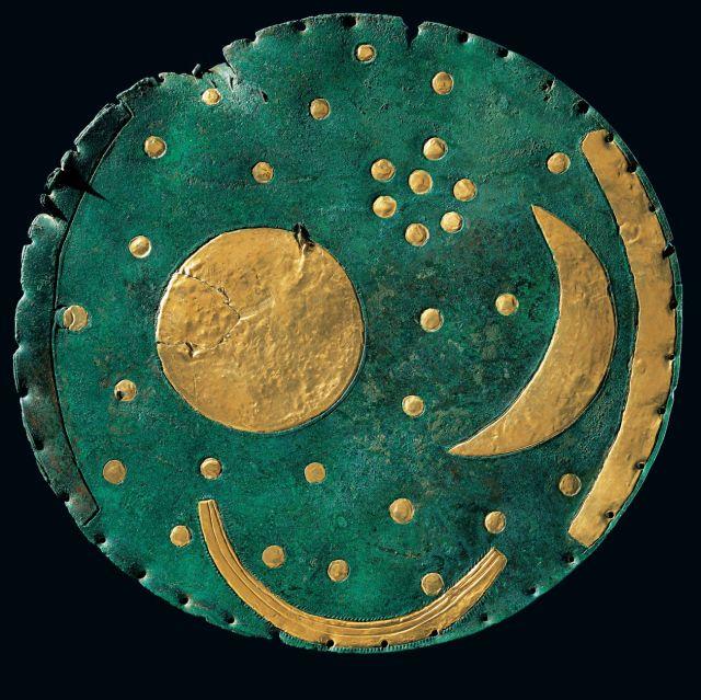 Die Himmelsscheibe von Nebra. Die Bronzescheibe ist grün, darauf als Goldblech die runde Sonne, der Mond, Sterne, eine Barke und ein Horizontbogen.