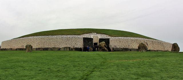Blick auf Newgrange. Heller Quarz auf der gsamten Front, darüber eine Deckschicht aus Erde mit Gras.
